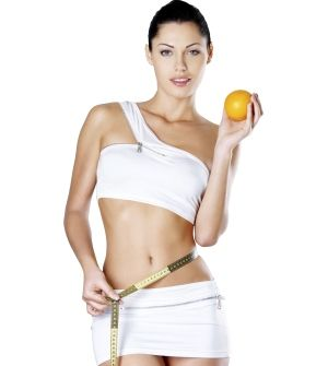 Healthy young woman with measuring tape and orange